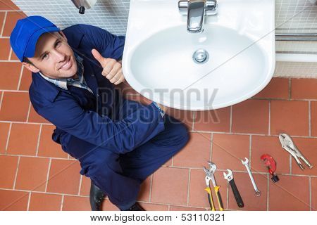 Smiling plumber repairing sink showing thumb up in public bathroom