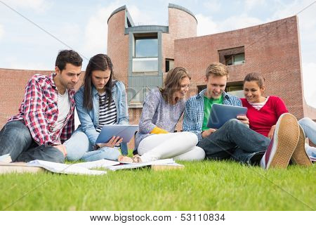 Group of young students using tablet PCs in the lawn against college building