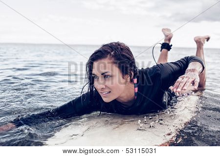 Young woman swimming over surfboard in the water at beach