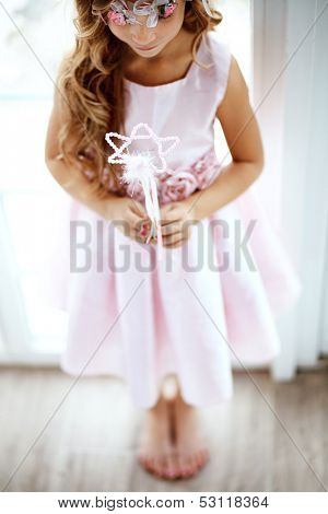 Beautiful little girl wearing fairy costume with magic wand shallow dof