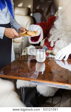 Cropped image of airhostess serving cookies to Santa in private jet