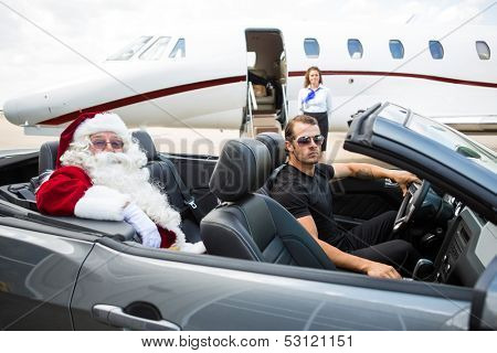 Portrait of Santa and driver in convertible with airhostess standing against private jet