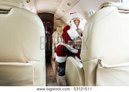 Bored Santa Claus sitting in private jet