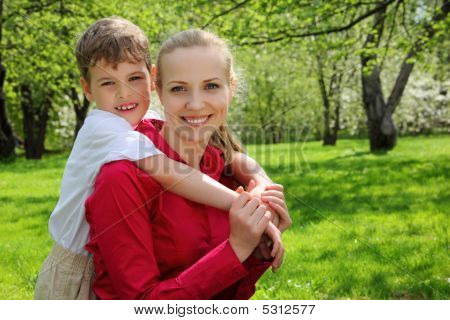 Son Embraces Behind Mother  In Park In Spring