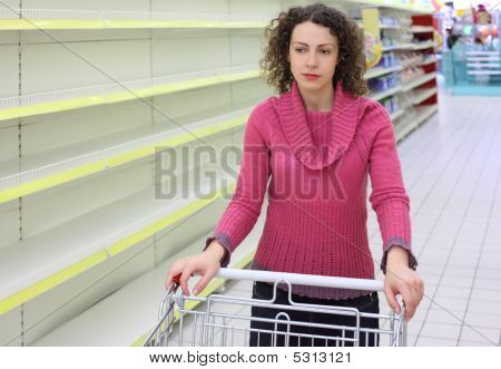 Young Woman With  Cart In Shop With Empty Shelves