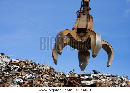 A Crane Grabber Up On The rusty Metal  Heap poster