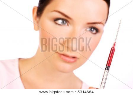 Woman Looking At Syringe Of Blood