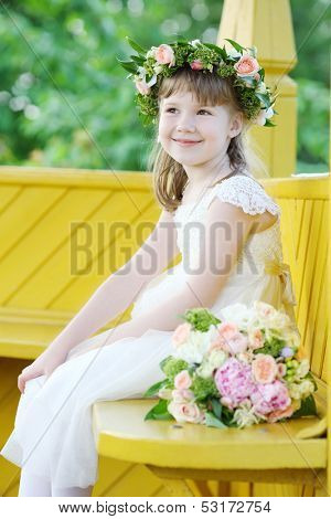 Little pretty girl in white dress and wreath sits in yelllow arbor and smiles.