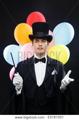 performance, circus, show, birthday party concept - magician in top hat with magic wand and colorful balloons showing trick