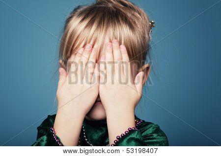 Little girl plays hide and seek