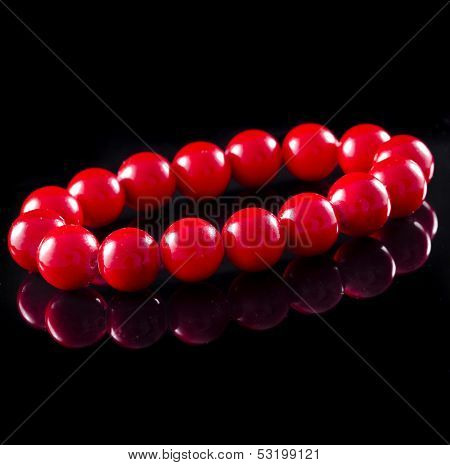 poster of beads of red coral with reflection isolated on black surface background