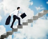 Young businessman climbing grey stairs on sky background poster