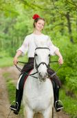 Smiling girl riding horse in the forest poster