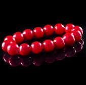 beads of red coral with reflection isolated on black surface background poster