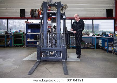 Mechanic going over the quality control checklist after a full revision and uphaul of a used forklift