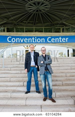 Two attendees of a congress at a trade fair posing on the steps leading to the front entrance of the convention center.