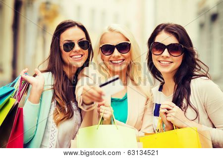 shopping and tourism concept - beautiful girls with shopping bags and credit card in ctiy poster