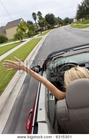 Young Woman Driving Convertible Car With Hand In The Air