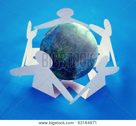 Paper people sitting around the globe holding hands.