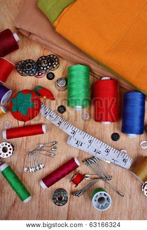 Background vertical with sewing items: buttons colorful fabrics material measuring tape bobbins buttons cloth safety pins needles pincushion thimble spools of thread poster