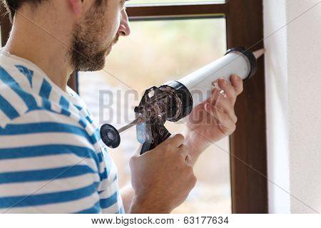 Man with caulking gun