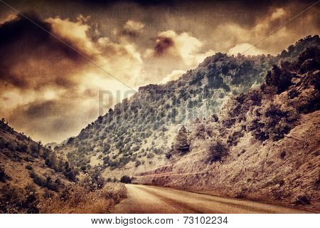 Grunge style photo of road passing between mountains, dramatic sunset cloudscape, beautiful landscape, overcast weather