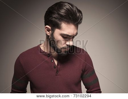 Closeup of a fashionable man wearing a burgundy sweater, looking down