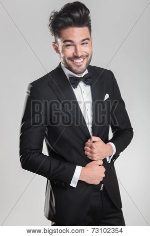 Happy young man wearing a tuxedo smiling for the camera while ajusting his jacket. on a grey background.