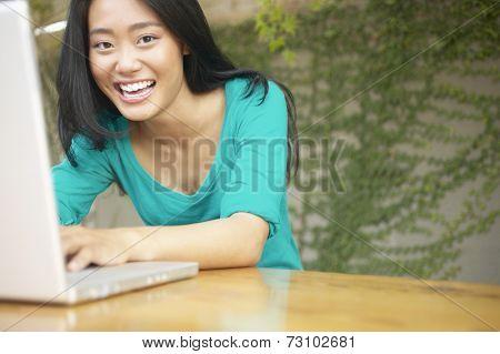 Asian woman using laptop outdoors