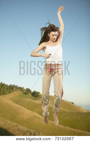 Full view of woman jumping in air while listening to music
