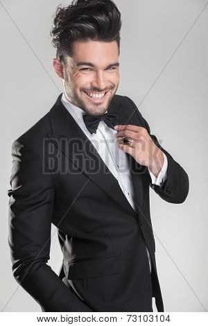 Elegant young man in tuxedo ajusting his bow tie while smiling for the camera. On grey background.