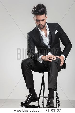 Elegant young man in tuxedo stitting on a stool while looking down, holding one hand on hei knee.