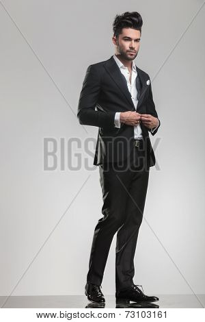 Full body image of an handsome young man looking away from the camera while closing his tuxedo.