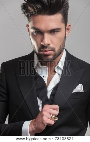 Close up picture of an elegant young man looking at the camera while ajusting his tuxedo. On grey background