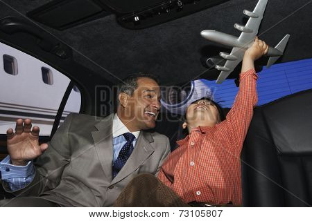 Father and son playing with an airplane in a limo