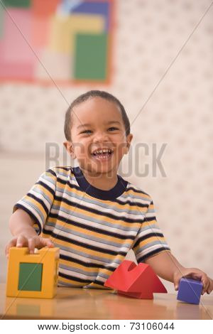 Portrait of young boy playing with blocks