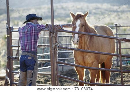 Young man in a cowboy outfit petting a horse