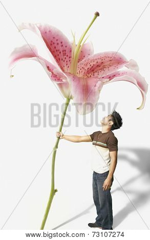 Young man holding a giant orchid