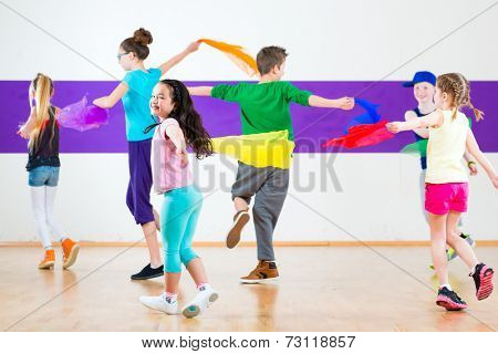 Children dancing modern group choreography with scarfs