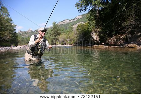 Closeup of fisherman fly fishing in freshwater river
