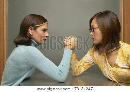 Businesswomen arm-wrestling