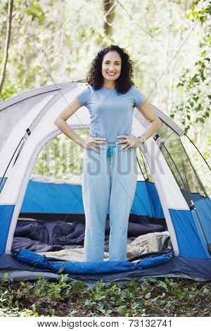 Woman standing next to tent