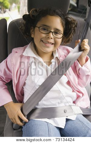 Girl fastening seatbelt in backseat of car