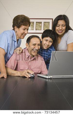 Multi-generational Hispanic family using laptop