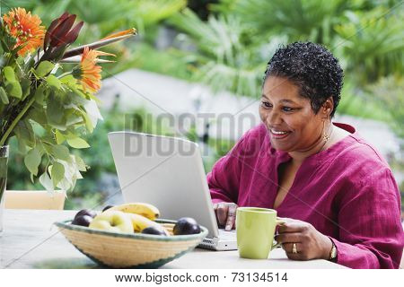 Middle-aged African woman using laptop outdoors