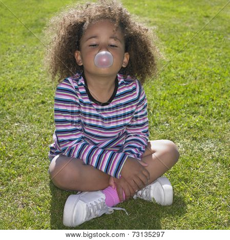 Young African girl sitting in grass blowing bubble gum