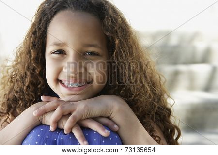 African girl with braces leaning chin on knees outdoors