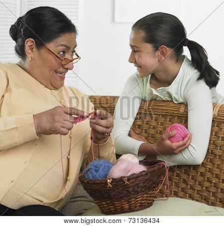 Hispanic grandmother and granddaughter with knitting supplies