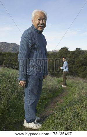 Senior man smiling on dirt path