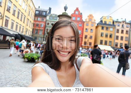 Asian woman taking self portrait selfie photo on Europe travel. Happy candid tourist on Stortorget, big square, Gamla Stan, the old town of Stockholm, Sweden. poster